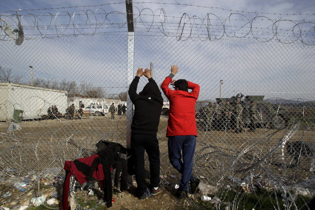 Two migrants look through a border fence towards the Macedonian side of the border, near the village of Idomeni, Greece March 6, 2016. Picture taken from the Greek side of the border. REUTERS/Alexandros Avramidis