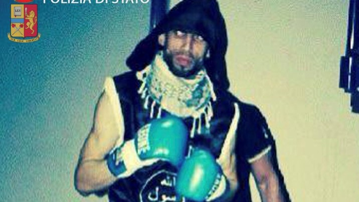 In an image released April 28, 2016, by Italian police, Moroccan-born Italian kickboxer Abderrahim Moutaharrik is seen wearing boxing gloves, shorts, a keffiyeh and a black shirt styled after the IS flag. (Italian Police)