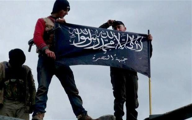 Rebels from al-Qaeda affiliated Jabhat al-Nusra waving their brigade flag CREDIT: AP