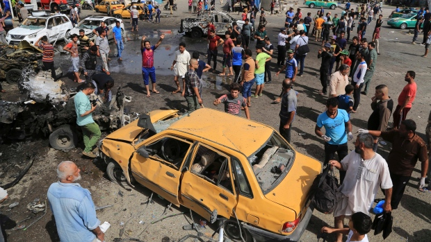 Security forces and citizens inspect the scene after a suicide car bombing hit a crowded outdoor market in Baghdad's eastern Shia neighbourhood of Sadr City, Tuesday. (Karim Kadim/Associated Press)