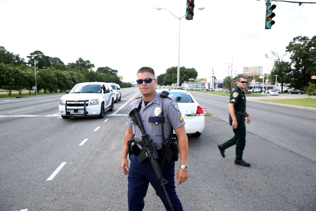 Police officers block off a road after the reported shooting of several officers in Baton Rouge, Louisiana, on Sunday (Joe Penney/Reuters)