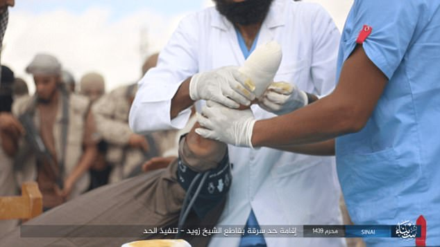Medical help: Two men in fresh scrubs are seen bandaging the stump after the hand had been cut off by the executioner