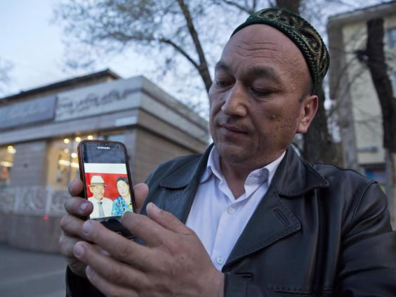 Omir Bekali displays a photo of his parents who he believes have now been interned in China (AP)